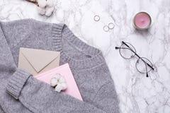 Suéter acogedor con el sobre, el cuaderno rosado y los anillos en el fondo de mármol fotografía de archivo