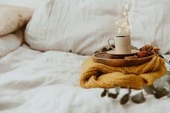 Suéter amarillo con café en cama Fotos de archivo