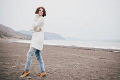 Suéter blanco que lleva hermoso y tejanos de la mujer joven que caminan en una playa sola Fotos de archivo libres de regalías