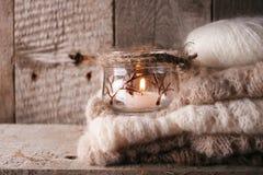 Suéter caliente en el banco rústico de madera, vela, escena acogedora acogedora de la tranquilidad Fin de semana del otoño de la  imagen de archivo