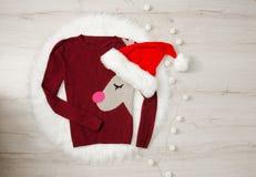 Suéter del concepto del ` s del Año Nuevo con el sombrero del reno y del ` s de Papá Noel Guirnalda, fondo de madera Fotografía de archivo