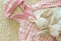 Suéter del ` s de Hildren y un conejo del peluche del juguete Imagenes de archivo