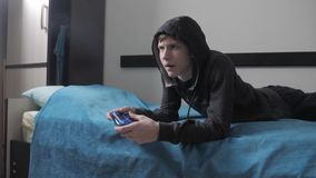 Suéter encapuchado de la forma de vida del hombre de la adolescencia joven y de la palanca de mando absorbente en videojuego en l almacen de metraje de vídeo
