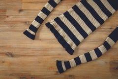 Suéter hecho punto en el fondo de madera Hecho a mano; Artesanía industria que hace punto Foto de archivo