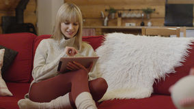 Suéter que lleva de la muchacha hermosa usando una tableta en casa Imágenes de archivo libres de regalías