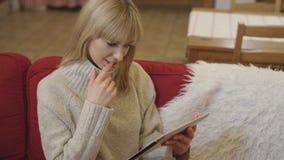 Suéter que lleva de la muchacha hermosa usando una tableta en casa Fotos de archivo