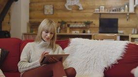 Suéter que lleva de la muchacha hermosa usando una tableta en casa Foto de archivo libre de regalías