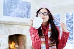 Suéter que lleva de la muchacha que bebe el café caliente Foto de archivo