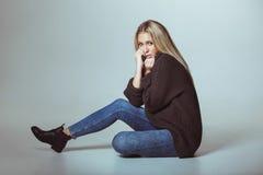 Suéter que lleva de la mujer atractiva que se sienta en piso Fotografía de archivo