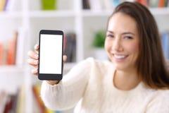 Suéter que lleva de la mujer que muestra la pantalla elegante del teléfono Imagen de archivo libre de regalías