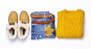 Suéter, tejanos, botas y hojas de otoño hechos punto anaranjados femeninos en endecha plana verde de la opinión superior del fond fotos de archivo libres de regalías