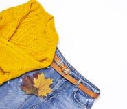 Suéter, tejanos y hojas de otoño hechos punto anaranjados femeninos en la endecha plana blanca de la opinión superior del fondo S imágenes de archivo libres de regalías
