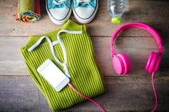 Suéteres, dispositivos elegantes del teléfono, bufandas, zapatos, botellas de agua con objeto del viaje Colocado en una tabla de  Fotografía de archivo libre de regalías