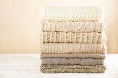 Suéteres en colores pastel doblados en la tabla de madera blanca Espacio del texto Fotografía de archivo libre de regalías