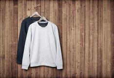 Suéteres en una pared de madera fotos de archivo