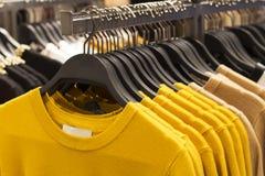 Suéteres hechos punto de lana amarillos de Ceilán de la tendencia que cuelgan en las suspensiones en la tienda, primer fotografía de archivo