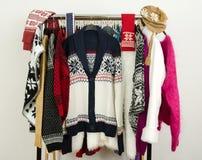 Suéteres lindos con los copos de nieve exhibidos en un estante Fotografía de archivo libre de regalías