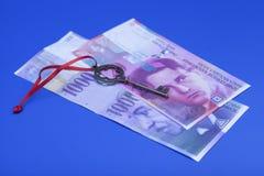 Suíço notas de 1000 e 20 francos com chave ao sucesso Imagem de Stock