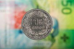 2 suíços Franc Coin com 50 suíços Franc Bill como o fundo Fotos de Stock Royalty Free