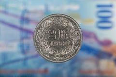 2 suíços Franc Coin com 100 suíços Franc Bill como o fundo Foto de Stock Royalty Free