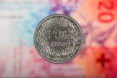 2 suíços Franc Coin com 20 suíços Franc Bill como o fundo Fotografia de Stock Royalty Free