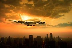 Самолет пассажирского самолета летая над городской сценой против красивого su Стоковые Изображения
