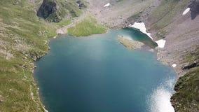 Su e giù la vista aerea del fuco del lago Barbellino un lago alpino naturale di estate La neve sta fondendosi stock footage