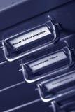 Su escritura de la etiqueta de la información en el cabinete de archivo Foto de archivo libre de regalías