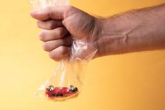 Su fondo giallo un pacchetto è trasparente che è un'automobile del giocattolo immagini stock libere da diritti