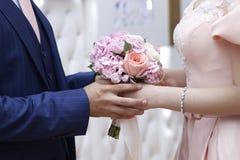 A su novio detiene a una novia en un vestido blanco del compromiso con un ramo nupcial en su mano Compromiso en el estilo rústico Foto de archivo libre de regalías