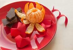 Su rosso il piatto è cioccolato, mandarino e due cuori fatti di Immagini Stock Libere da Diritti
