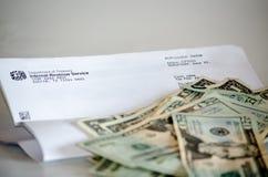 Letra y dinero del IRS imagenes de archivo