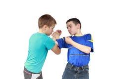 Su un fondo bianco due i ragazzi in abbigliamento degli abiti sportivi sta eseguendo i trucchi Fotografia Stock