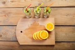 Su un fondo di legno sono i pezzi di arancia accanto ai vetri in cui sono i pezzi di frutta Fotografia Stock