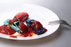 Su un fondo grigio c'è un piatto bianco su cui ci sono tre automobili infradiciate con ketchup fotografia stock