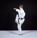 Su un fondo nero, battiti di un atleta di karatè con un ginocchio Fotografie Stock Libere da Diritti