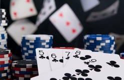 Su un fondo nero, sulle carte volanti per il gioco, su un primo piano, su un insieme alla vittoria e su una pila di chip da scomm immagini stock