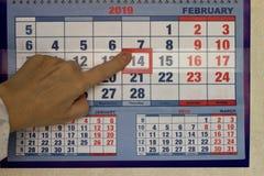 Su un pezzo del calendario, il dito femminile indica la data del 14 febbraio immagine stock libera da diritti