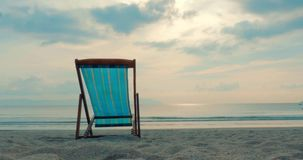 Su un primo piano tropicale Chaise Longue Aainst della spiaggia il mare e un bello tramonto o alba, lungo la costa tropicale stock footage