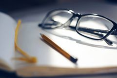 Su un taccuino aperto sono i vetri e una matita fotografie stock