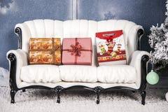 Su una bugia dei regali del sofà di bianco Immagini Stock