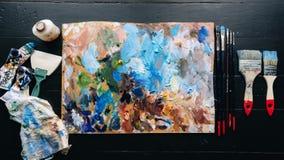 Su una bugia di legno della tavola una tavolozza, spazzole, pitture Fotografie Stock Libere da Diritti