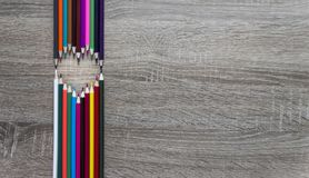 Su una bugia di legno delle matite del fondo che forma un cuore Fotografie Stock Libere da Diritti