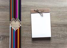 Su una bugia di legno delle matite del fondo che forma un cuore vicino ad un cuscinetto dell'arco del libro di schizzo della cart Immagini Stock Libere da Diritti