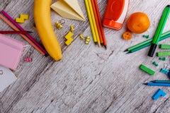 Su una tavola è una disposizione delle matite multicolori, delle cucitrici meccaniche, di un taccuino, dei pastelli colorati e di fotografia stock libera da diritti