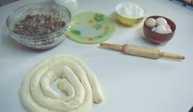 Su una tavola bianca una ciotola con le uova e la farina, aspetta per essere acciambellata ed accanto al matterello Vista da sopr Fotografia Stock