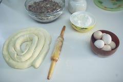 Su una tavola bianca una ciotola con le uova e la farina, aspetta per essere acciambellata ed accanto al matterello Vista da sopr Immagine Stock