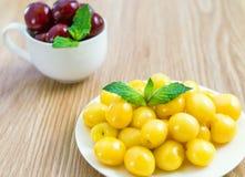Su una tavola c'è un piattino con una ciliegia gialla Immagine Stock