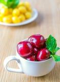 Su una tavola c'è una tazza con una ciliegia Fotografia Stock Libera da Diritti