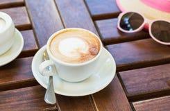 Su una tavola marrone di legno è una tazza con cappuccino, un cappello, vetri Estate, caffè, resto Fotografia Stock
